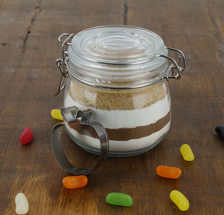 Glass jar containing layered cookie mix with apple shaped cookie cutter