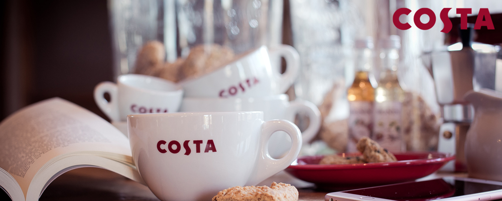 Banner photo showing a Costa capuccino, espresso shot cups on a table with french presse and biscuits