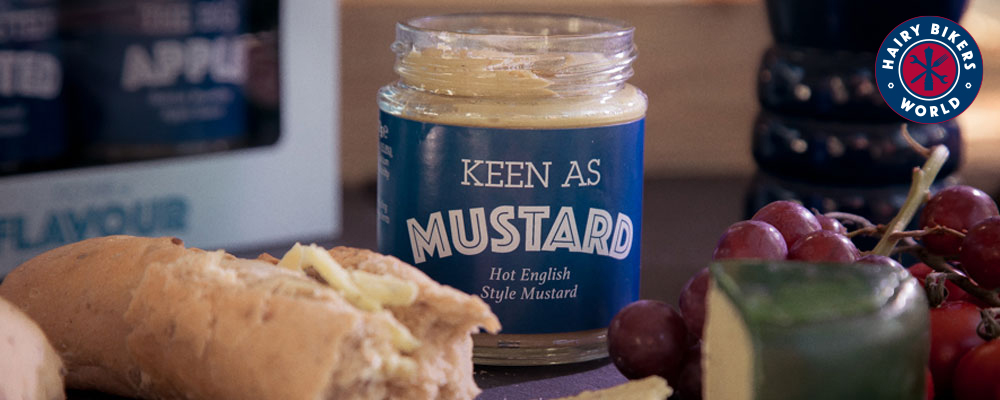 A jar of 'Keen as mustard' from the Hairy Bikers range of gifts, accompanied by bread, cheese and red grapes