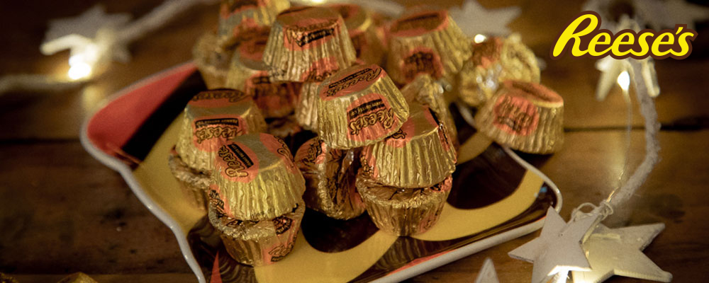 Individually gold foil wrapped Reese's peanut butter cup confectionery on a Reese's serving plate