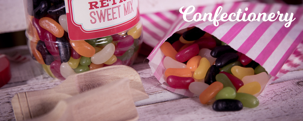 A plastic tub and a bag of retro jelly bean sweets with mini wooden sweetie scoops.