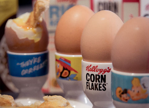 Boiled eggs lined up in Kellogg's egg cups
