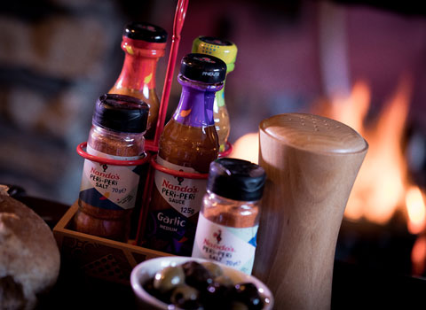 Nando's sauces and salts with a carrier and olives