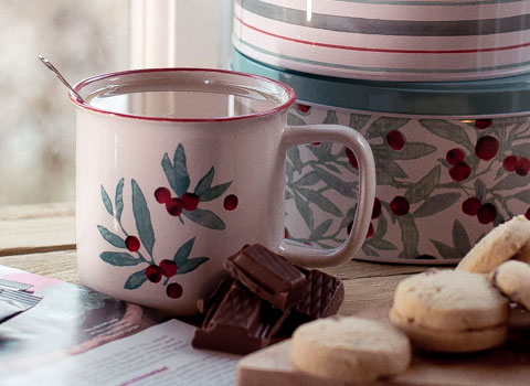 Leaf and berry design tin mug with biscuit tin behind and shortbread in front
