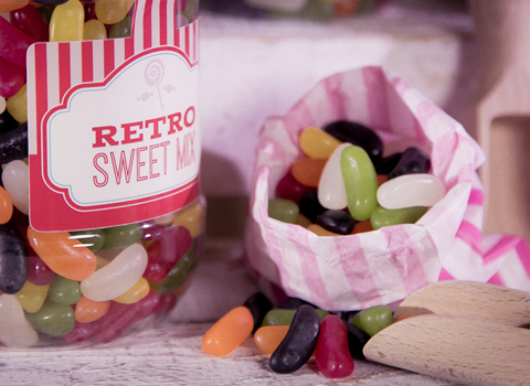 Retro sweets plastic tub and a stripey paper bag of jelly beans